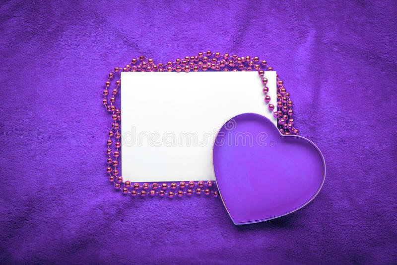Heart with a blank card on violet background.  stock photography