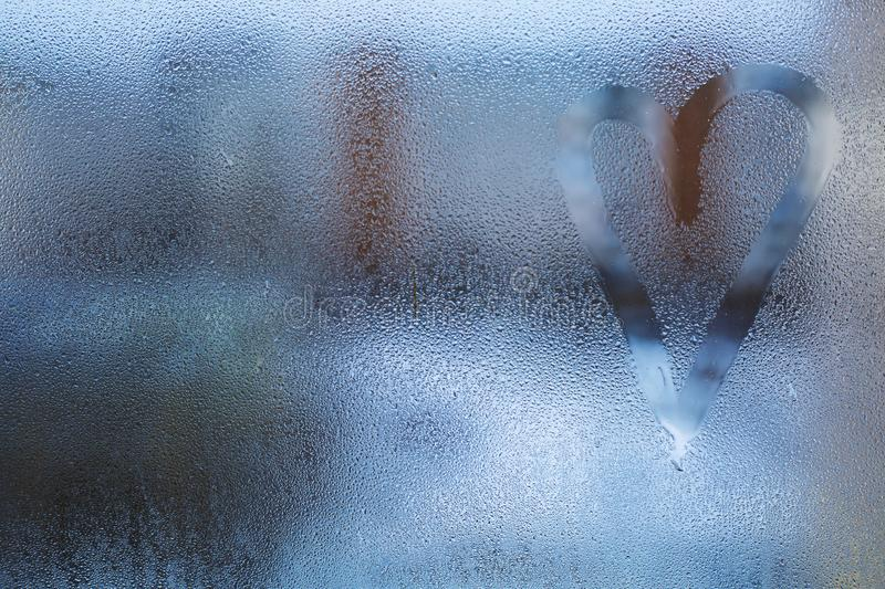 Heart is painted on the misted glass in the winter stock photos