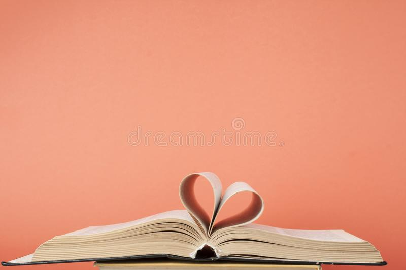 Heart from book page on red background.Free copy space. Education concept. Close up heart shape from paper of book on red background. Free copy space.Education stock image