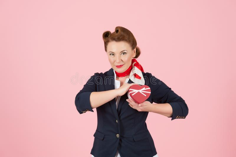 Heart red box in hand of pin-up styled red hair woman. Attractive lady sending her heart with love. Box for valentine presents stock image