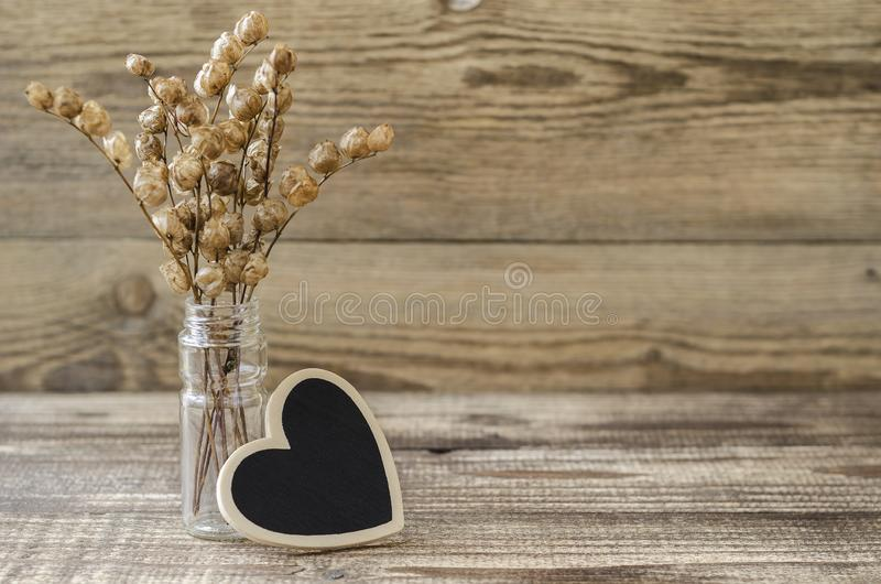 Heart with a bunch of dried flowers on a wood background 3 stock photography