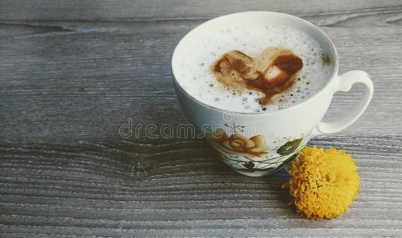 A heart from c4offee in the milk. Beautiful cup with yellow flower on it and near it. Wooden background. royalty free stock photos