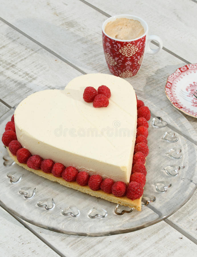Heart Cake. Romantic heart shaped mothers day cake with raspberries, Setting with cup of coffee on a white table