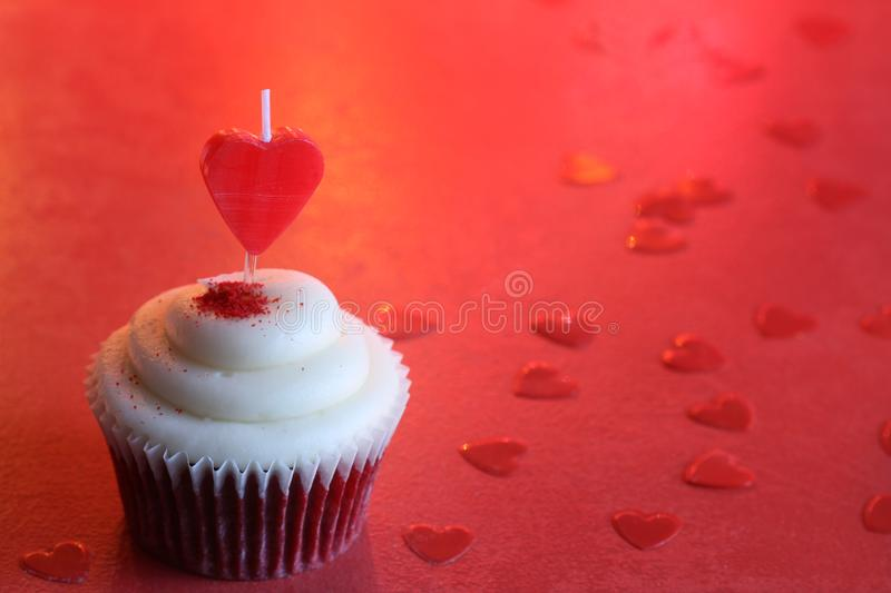 Heart candle in the cupcake on the love abstract defocused valentines day red background. Closeup stock photography