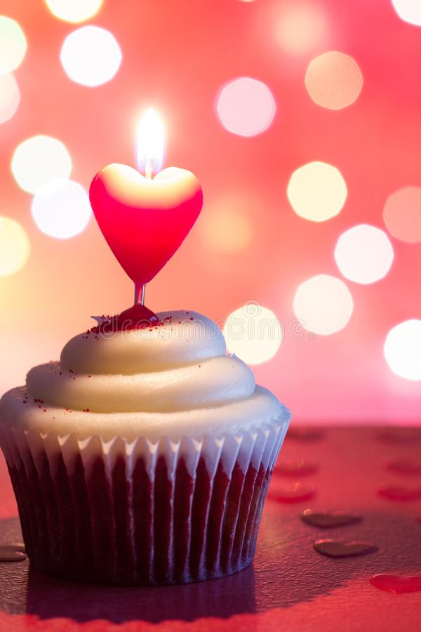 Heart candle in the cupcake on the love abstract defocused valentines day red background. Closeup royalty free stock images