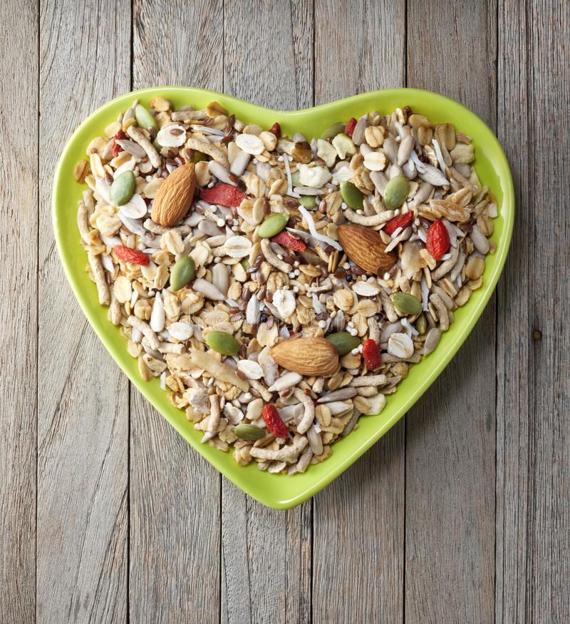 Heart Cereal Fruit Granola Muesli Bowl. A heart shaped bowl of healthy granola or muesli on a rustic wood background stock images