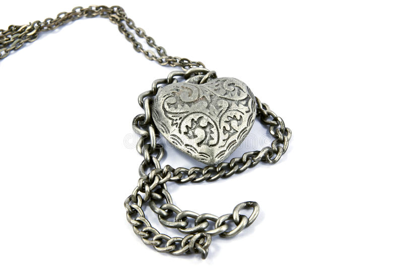 Heart charm necklace. Old worn silver heart charm necklace stock images