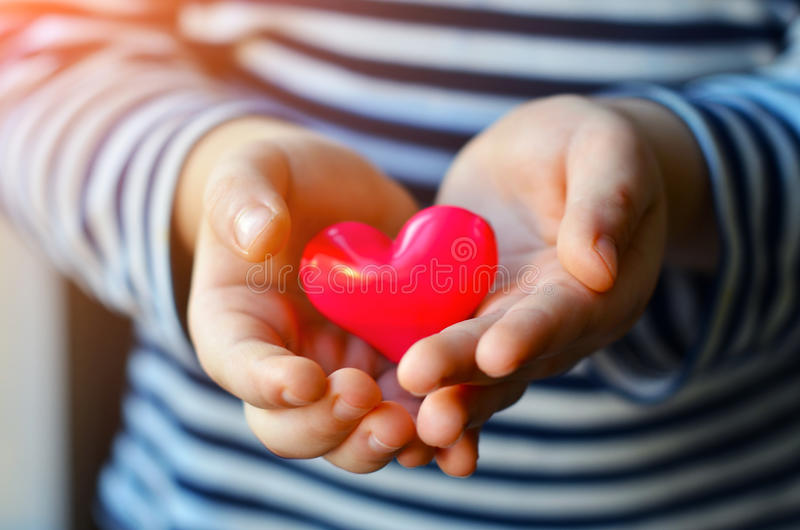 Heart in child`s hands. Child holding a small pink heart. symbol of love, family, hope. Backgrounds for cards on Valentine`s Day. Backgrounds for social posters royalty free stock photo