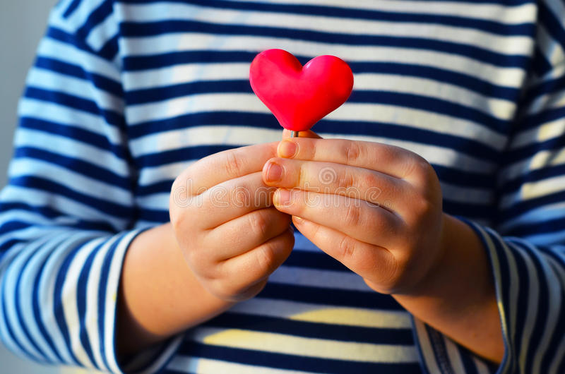 Heart in child`s hands. Child holding a small pink heart. symbol of love, family, hope. Backgrounds for cards on Valentine`s Day. Backgrounds for social posters royalty free stock photos