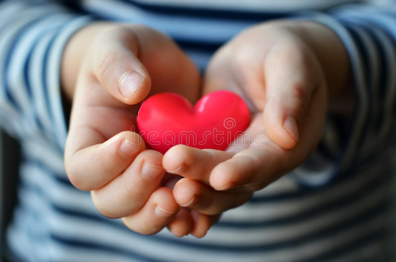 Heart in child`s hands. Child holding a small pink heart. symbol of love, family, hope. Backgrounds for cards on Valentine`s Day. Backgrounds for social posters stock images