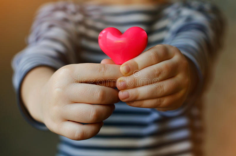 Heart in child`s hands. Child holding a small pink heart. symbol of love, family, hope. Backgrounds for cards on Valentine`s Day. Backgrounds for social posters stock photo
