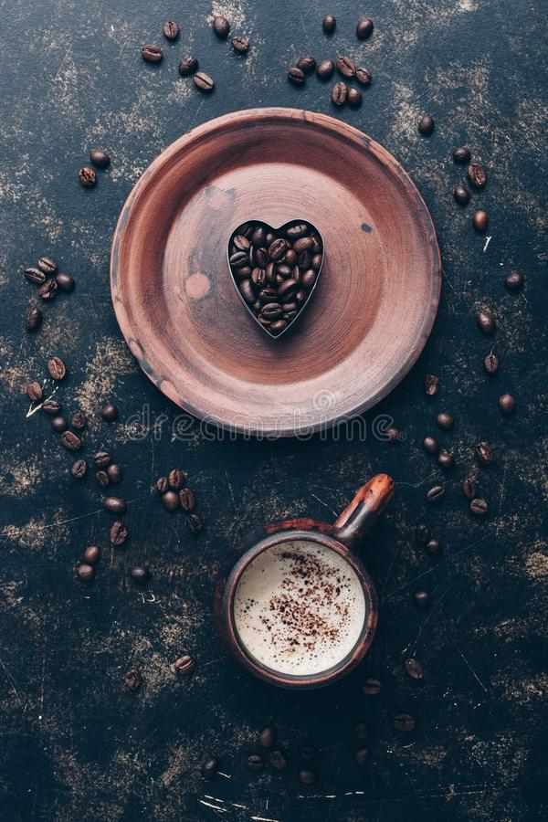 Heart of coffee beans and hot coffee drink in a vintage cup on a rustic dark background. Valentine`s Day.Top view, place for text stock photography