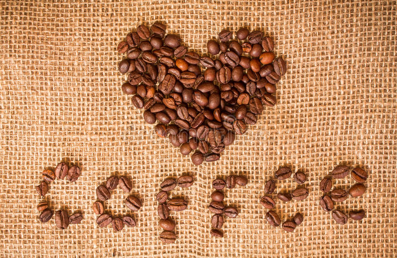 Heart of coffee beans on sackcloth royalty free stock photography