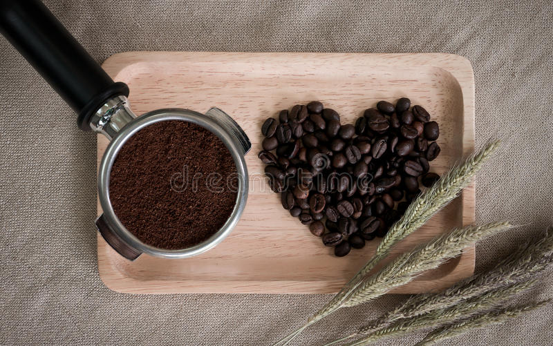 Heart from coffee beans and wooden spoons with coffee maker prepared on the desktop. Heart from coffee beans and wooden spoons with coffee maker prepared on the stock photography
