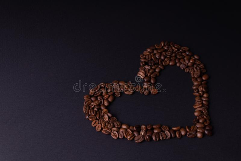 The heart of coffee is located to the left of the center of the background.  royalty free stock photography