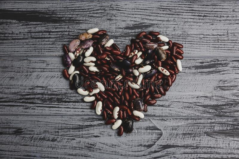 Heart from colorful kidney beans on a wooden table royalty free stock images