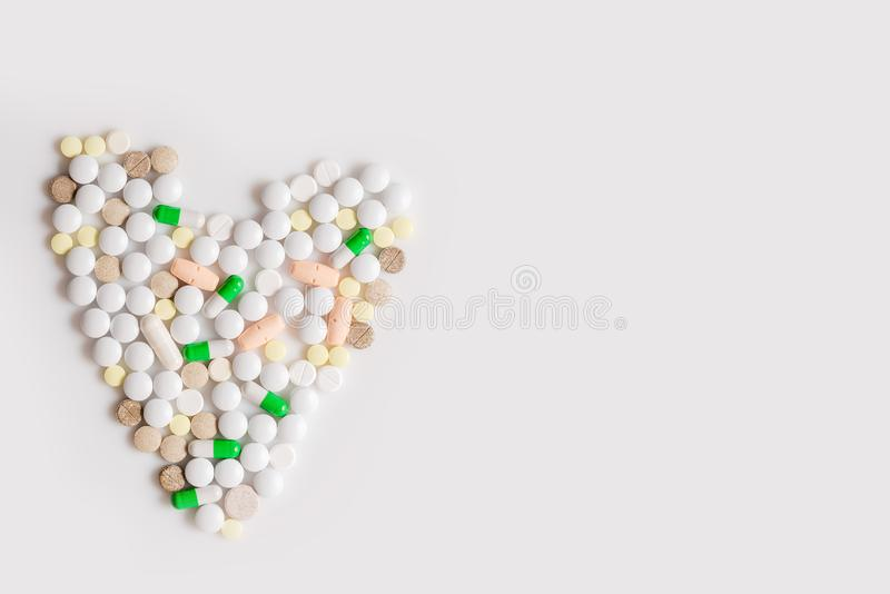 Heart from colorful pills at white background stock photo