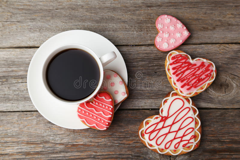 Heart cookies with cup of coffee on a grey wooden background royalty free stock photography