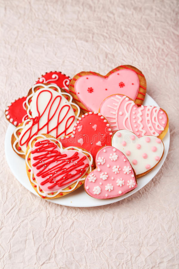 Heart cookies on white plate on the pink paper background stock photos