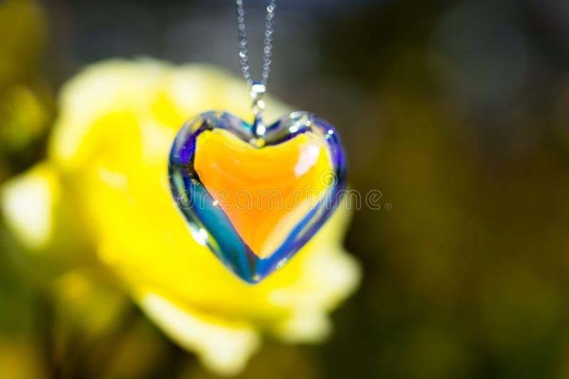 Heart crystal glass refract sunlight - rose garden background. AT 1/4/2019 in Rose garden stock images