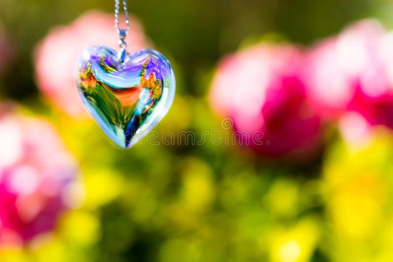 Heart crystal glass refract sunlight - rose garden background. AT 1/4/2019 in Rose garden stock photography