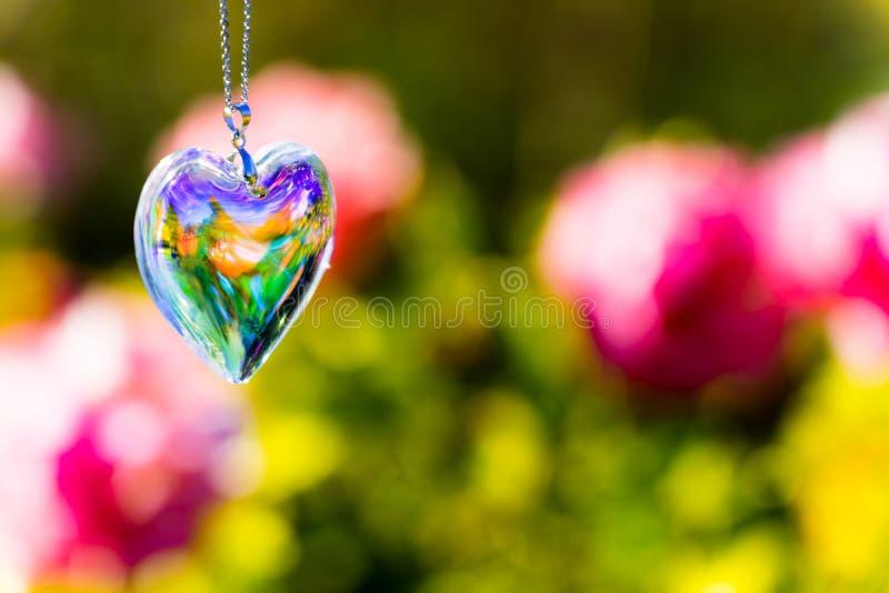 Heart crystal glass refract sunlight - rose garden background. AT 1/4/2019 in Rose garden stock photos