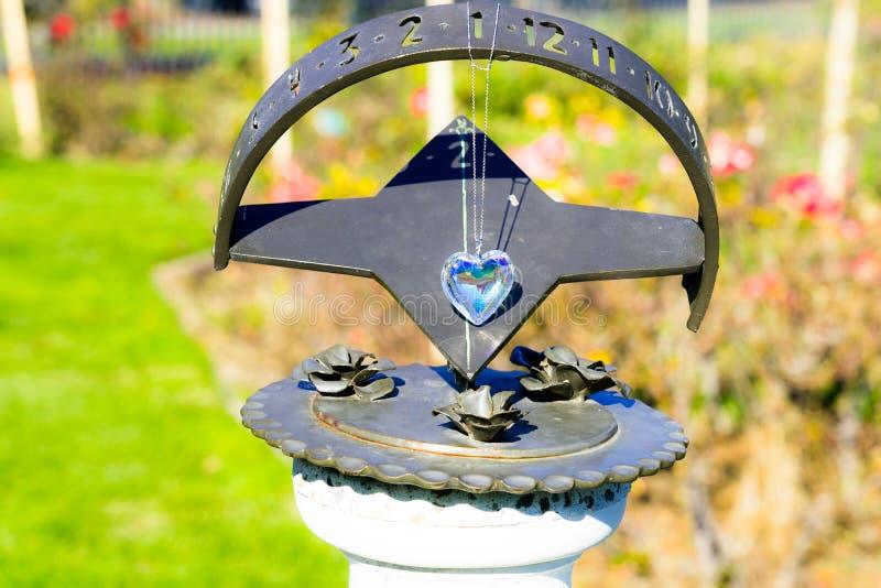 Heart crystal glass refract sunlight - sunlight clock background. AT 1/4/2019 in Rose garden stock image