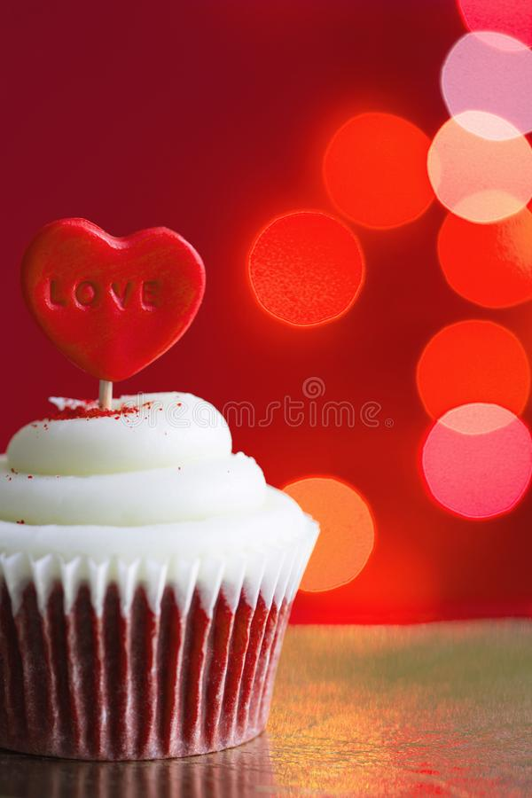 Heart in the cupcake on the love abstract defocused valentines day red background. Closeup stock photos