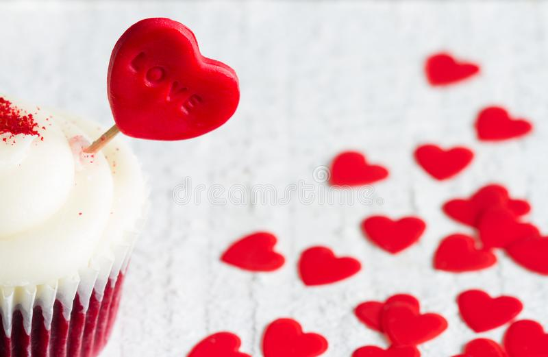 Heart in the cupcake on the love abstract white valentines day red background. Closeup royalty free stock image