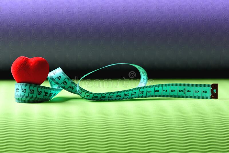 Heart decoration and flexible ruler lying on yoga mat stock photography
