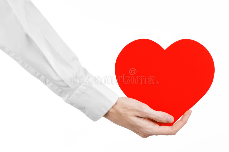 Heart Disease and Health Topic: hand doctor in a white shirt holding a card in the form of a red heart isolated. On a white background, studio royalty free stock images