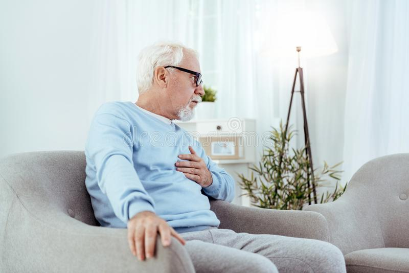 Upset senior man feeling heart discomfort. Heart disease. Uneasy senior man touching chest and sitting in armchair stock photography