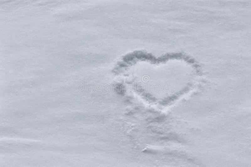 Heart drawing in the snow. Heart shape on fresh pristine snow. Winter background stock photo