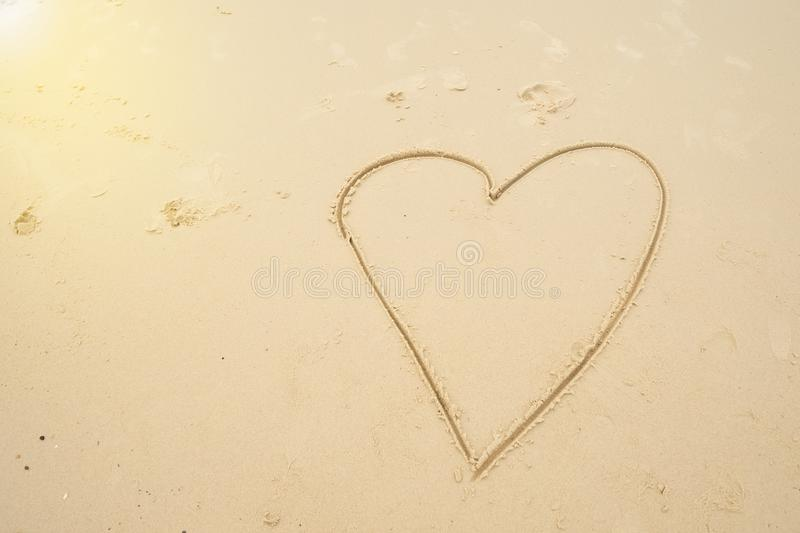 Heart drawn on beach sand at the sea stock photo