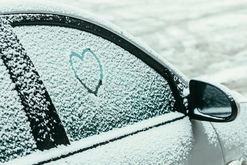 Heart drawn on a car windshield covered with fresh snow stock photo