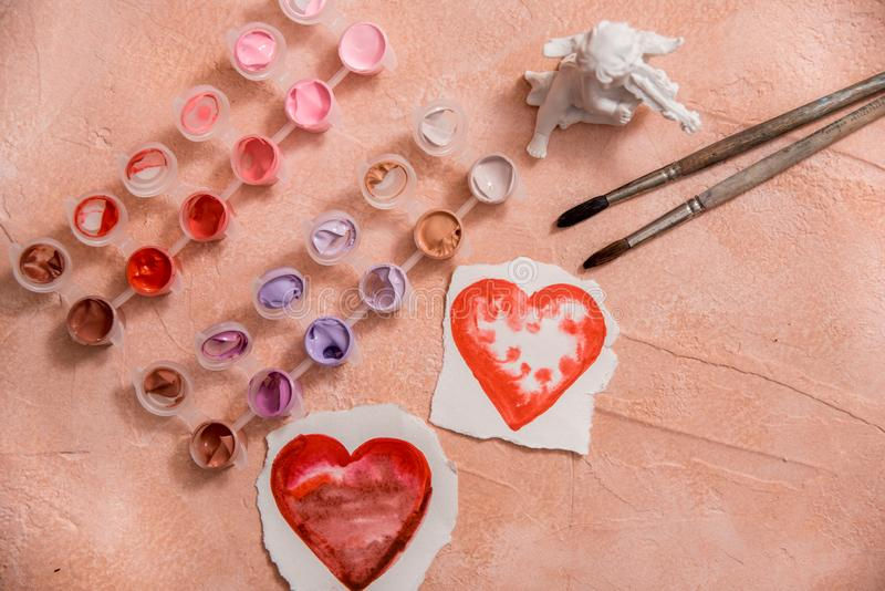 A heart drawn by lipstick, with more hearts made of powder and blush. 'Love makeup ' valentine card with a professional brush. Colored paints and brushes stock photos