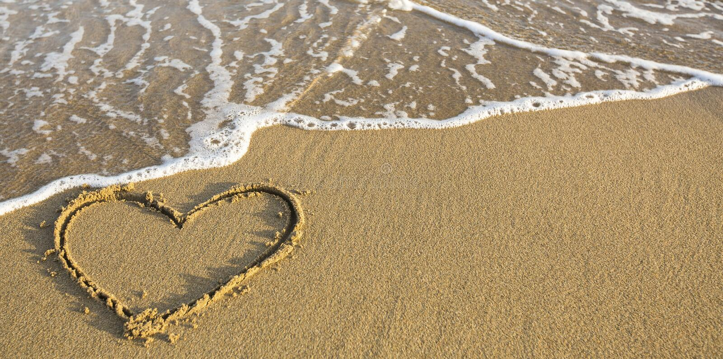 Heart drawn on ocean beach sand. Romantic. royalty free stock photography