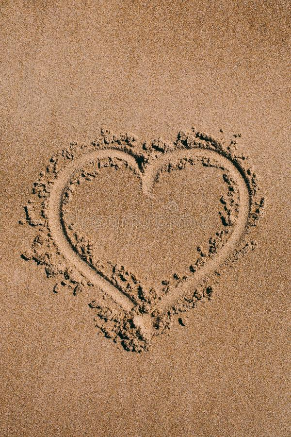 Heart drawn in the sand. Beach background with heart drawing. Heart shape love symbol as background. stock photo