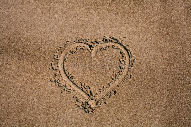 Heart drawn in the sand. Beach background with heart drawing. Heart shape love symbol as background. royalty free stock photo