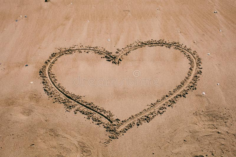 Heart drawn in the sand. Beach background with heart drawing. Heart shape love symbol as background. royalty free stock images