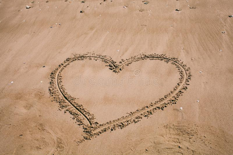 Heart drawn in the sand. Beach background with heart drawing. Heart shape love symbol as background. stock images
