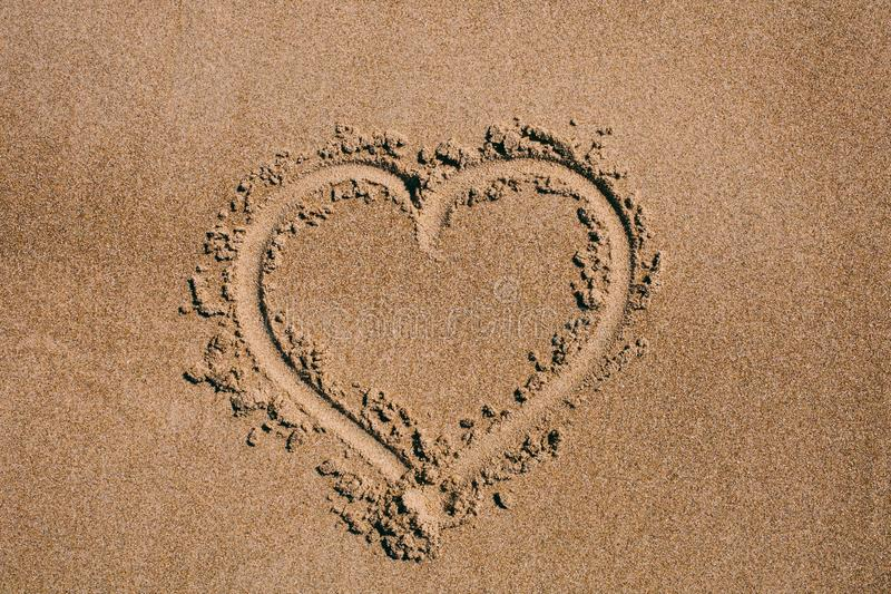 Heart drawn in the sand. Beach background with heart drawing. Heart shape love symbol as background. stock image