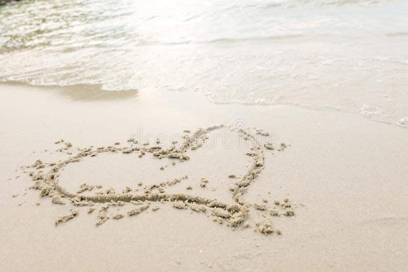 Heart drawn on a sand of beach with the wave of the sea in the bright sunlight. royalty free stock image