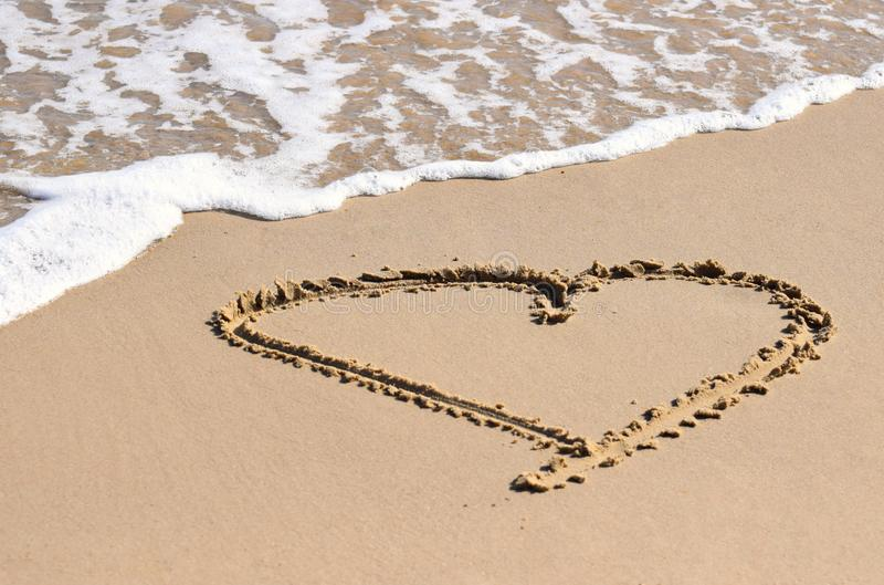 Heart drawn in the sand. A love heart drawn in the sand on a beach with the sea coming in stock photo