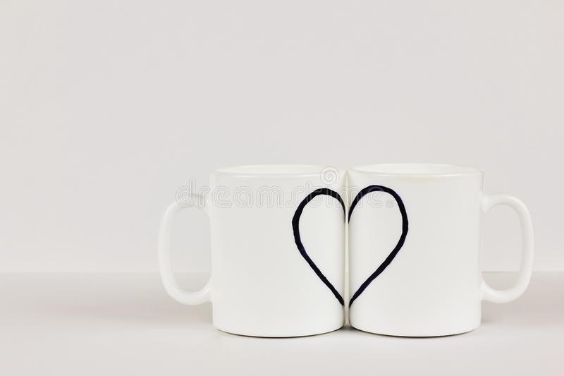 Heart drawn on two cups on white background. Valentine`s day, love, couple, wedding concept stock image