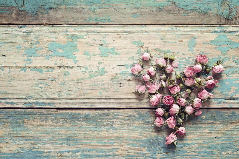 Heart from dried rose flowers on the turquoise old wooden background with copy space. Flowers composition. stock photos