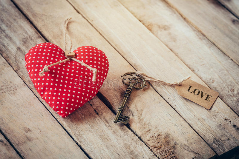 Heart fabric and vintage key with tag label LOVE on wood table b stock photo