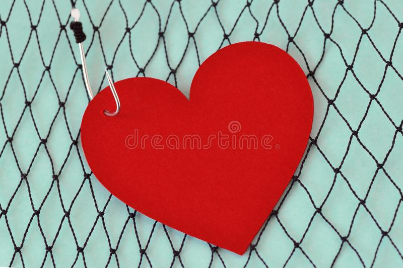 Heart on fish hook on fishing net - Love concept. Heart on fish hook on fishing net. Love concept royalty free stock images