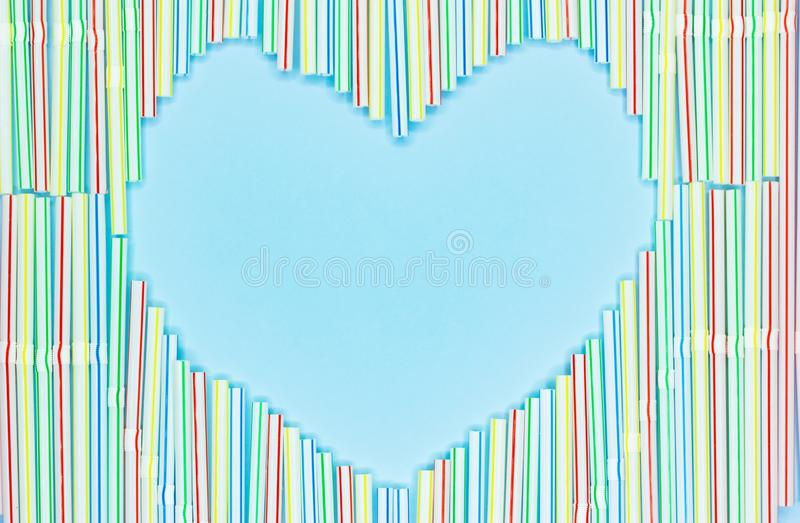 Heart frame of colored plastic straws or cocktail tubules on light blue background with copy spase royalty free stock photography