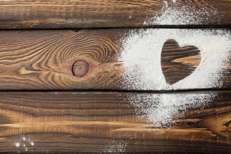 Heart free space. Heart made of flour on a wooden background stock images